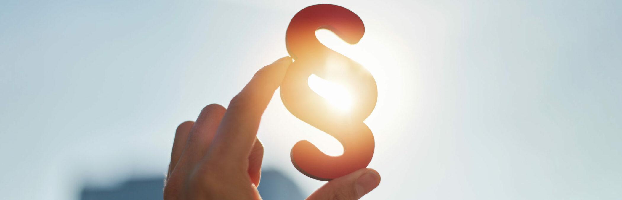 § 2b UStG: Eine Hand hält ein Paragraphenzeichen in die Sonne.