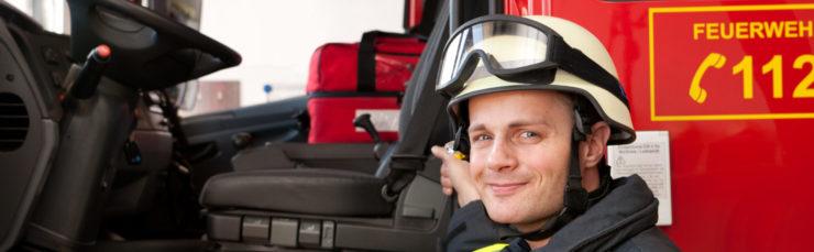 Feuerwehr: Ein Feuerwehrmann steht vor seinem Einsatzfahrzeug.