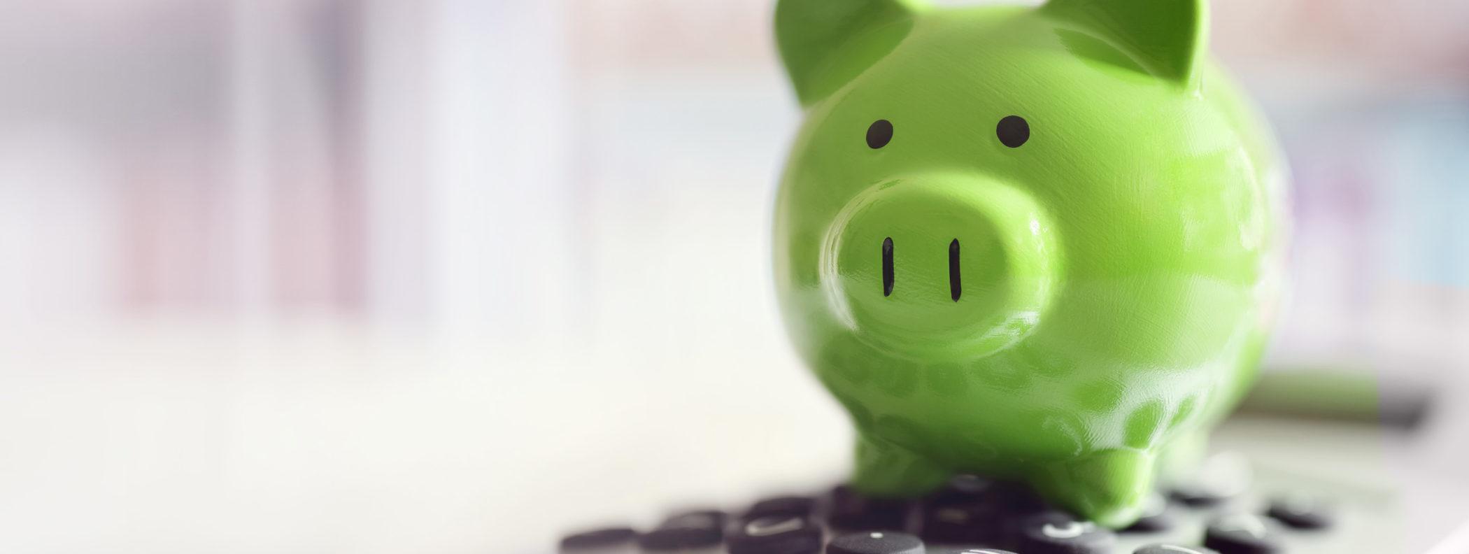Gebührenkalkulation: Sparschwein steht auf einem Taschenrechner.