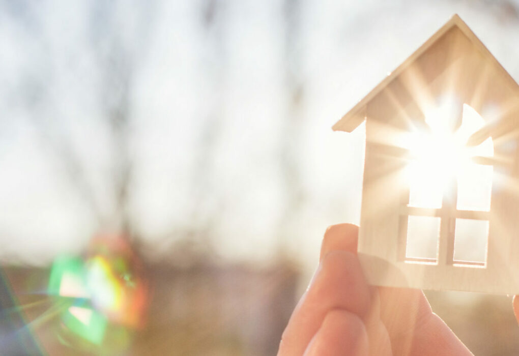 Haushaltsumsetzung: Eine Hand hält ein kleines Holzhaus in die Sonne.