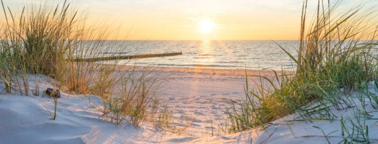 Kur- und Fremdenverkehrsabgaben: Stand und Meer mit Sonne im Hintergrund