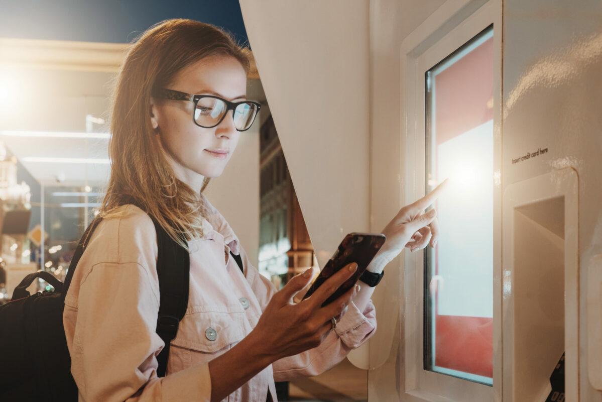 Moderne Bürgerbüros und Online-Dienste: Frau kauft an einem modernem Automaten Tickets.