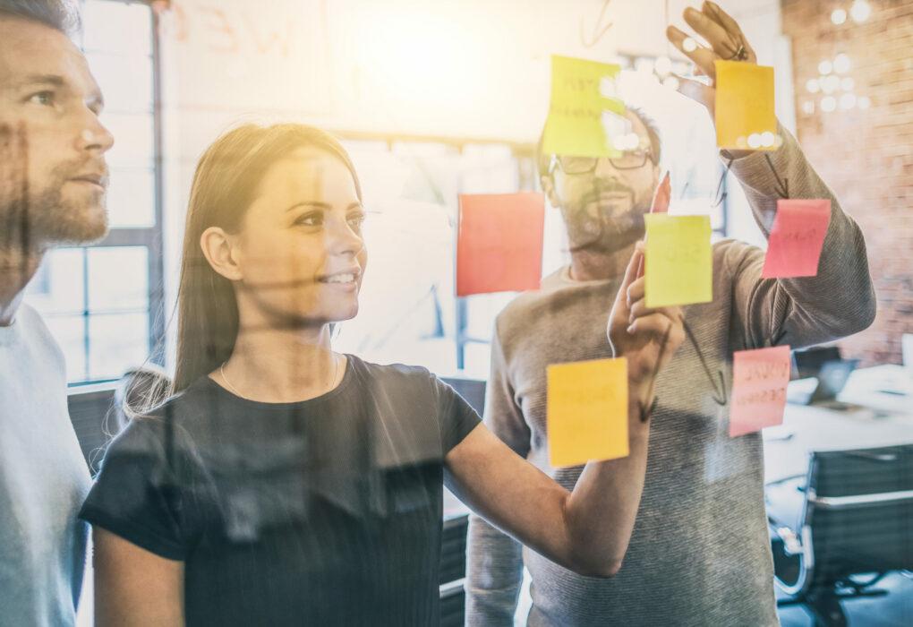 Organisation und Management: Managementteam wertet in einem Meeting verschiedene Postits aus.