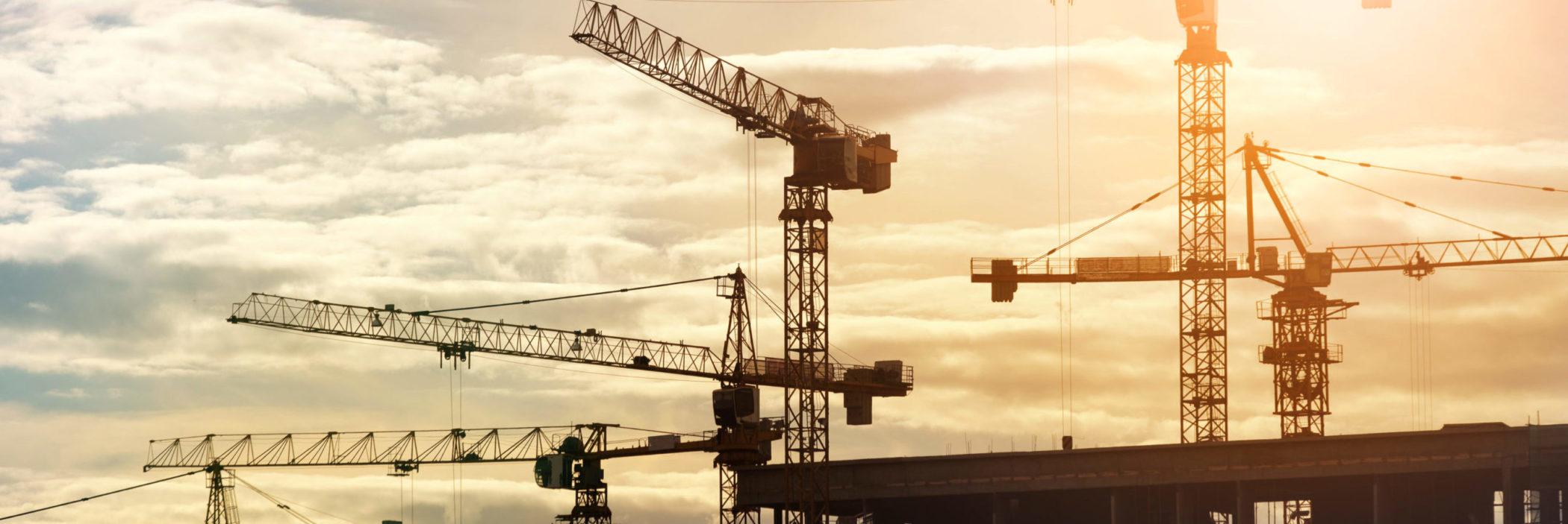 WiBe Hochbau: Kräne stehen auf einer Baustellen im Sonnenaufgng.